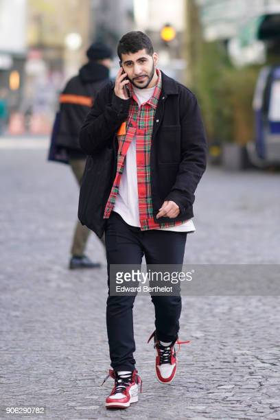 A guest wears a black jacket a checked red shirt a white top black pants red sneakers outside Off White during Paris Fashion Week Menswear Fall...