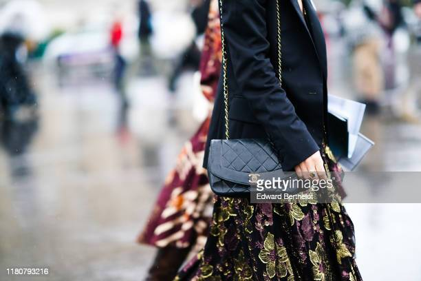 Guest wears a black jacket, a floral print dress, a Chanel bag, outside Chanel, during Paris Fashion Week - Womenswear Spring Summer 2020, on October...