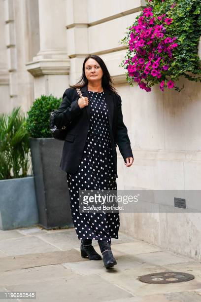 Guest wears a black jacket, a navy blue dress with printed white polka dots, black leather boots, during London Fashion Week September 2019 on...