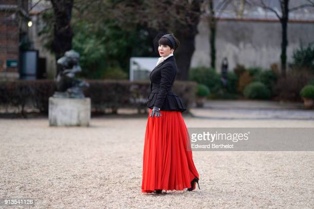 A guest wears a black jacket a red pleated skirt after Dior during Haute Couture Spring/Summer 2018 on January 22 2018 in Paris France