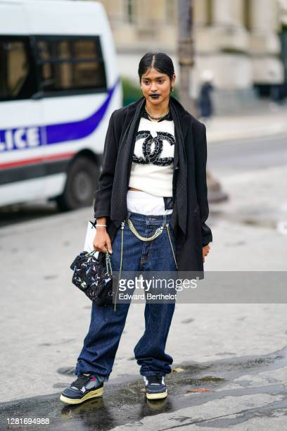 Guest wears a black jacket, a white Chanel logo pullover, blue oversized denim jeans pants, sneakers, a fluffy Chanel bag, earrings, a necklace,...