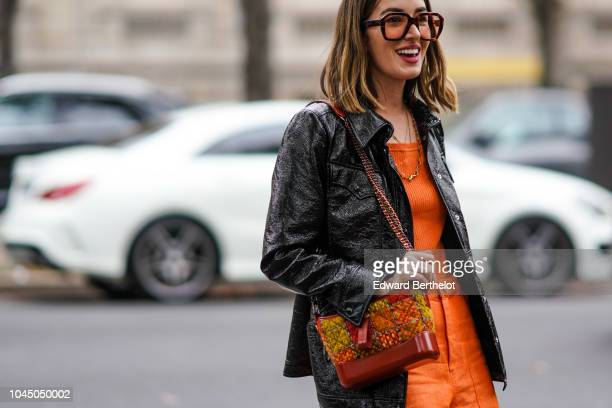 A guest wears a black jacket an orange top flare pants a Chanel bag outside Miu Miu during Paris Fashion Week Womenswear Spring/Summer 2019 on...