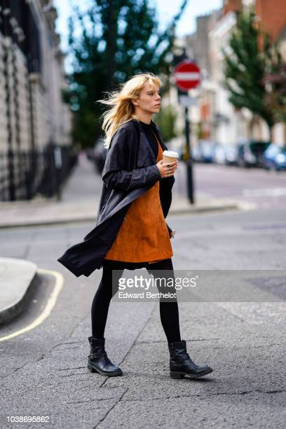A guest wears a black jacket and orange suede dress black tights black leather boots during London Fashion Week September 2018 on September 16 2018...