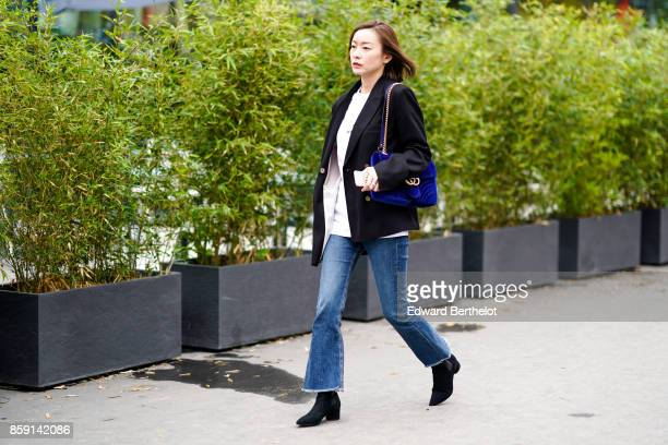 A guest wears a black jacket blue jeans black boots and midnight blue Gucci bag outside Ann Demeulemeester during Paris Fashion Week Womenswear...