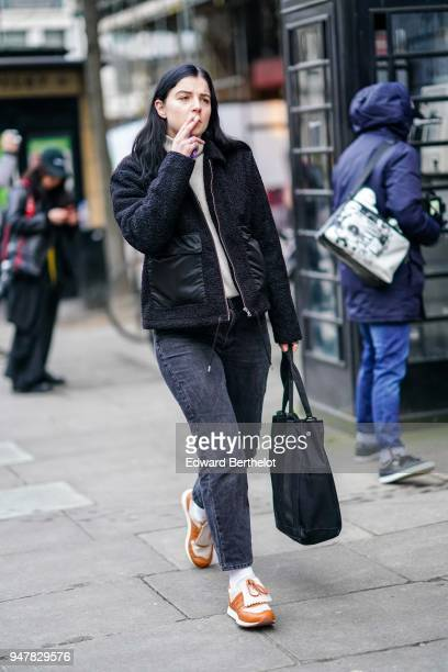 A guest wears a black jacket orange sneakers gray jeans during London Fashion Week Men's January 2018 at on January 6 2018 in London England