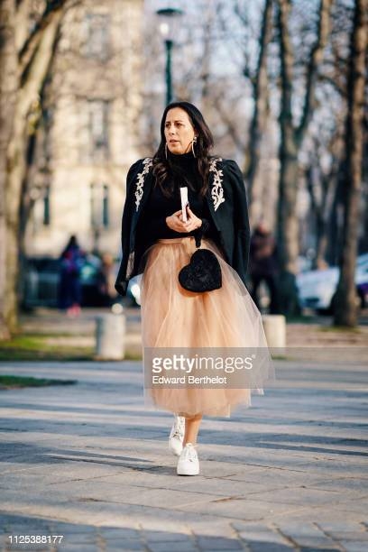 A guest wears a black jacket pink lace skirt a black bag shaped as a heart white sneakers during Paris Fashion Week Haute Couture Spring Summer 2020...