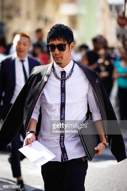 A guest wears a black jacket sunglasses a Christian Dior 'atelier' white shirt a black clutch outside Dior during Paris Fashion Week Menswear...