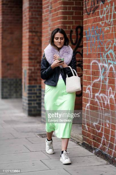 A guest wears a black jacket with pale purple faux fur collar a white bag made of pearls a green satin skirt white sneakers during London Fashion...