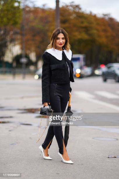 Guest wears a black jacket with white large collar, black slit pants, a black leather crocodile pattern bag, white pointy shoes, holds an umbrella,...