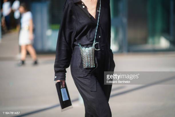 A guest wears a black jumpsuit a metal mesh bag outside Acne during Paris Fashion Week Haute Couture Fall/Winter 2019/2020 on June 30 2019 in Paris...