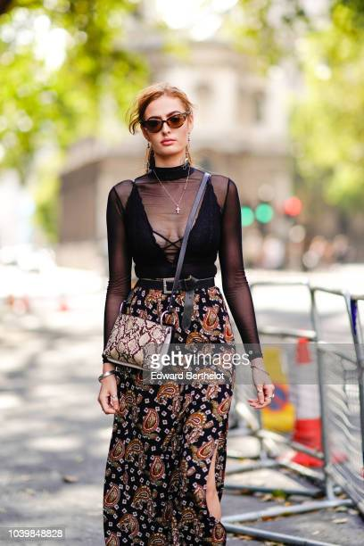 A guest wears a black lace mesh top a floral print skirt brown leather boots a snake print bag during London Fashion Week September 2018 on September...