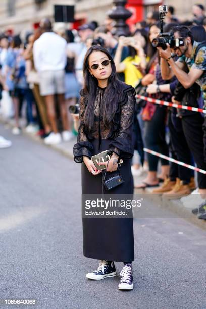 A guest wears a black lace mesh top a VLTN black rectangular rigid clutch a black skirt sneakers outside Valentino during Paris Fashion Week Menswear...