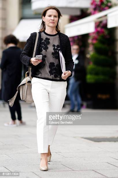 A guest wears a black lace mesh top with embroidery white pants shoes outside the Schiaparelli show during Paris Fashion Week Haute Couture...