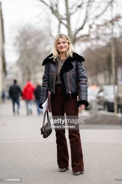 A guest wears a black leather aviator jacket flare pants a Fendi bag outside Acne during Paris Fashion Week Menswear F/W 20192020 on January 20 2019...