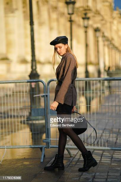 Guest wears a black leather beret hat, a blazer jacket with printed houndstooth patterns, a bag, tights, shoes, outside Louis Vuitton, during Paris...