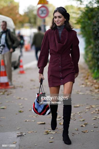 A guest wears a black leather beret hat a purple red dress black thigh high boots a bag outside Issey Miyake during Paris Fashion Week Womenswear...