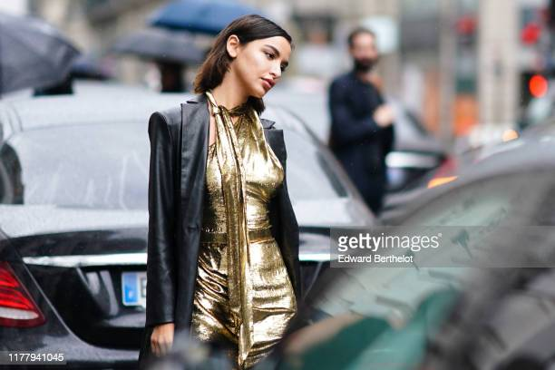 A guest wears a black leather coat a golden sequined glitter shiny dress outside Ralph Russo during Paris Fashion Week Womenswear Spring Summer 2020...