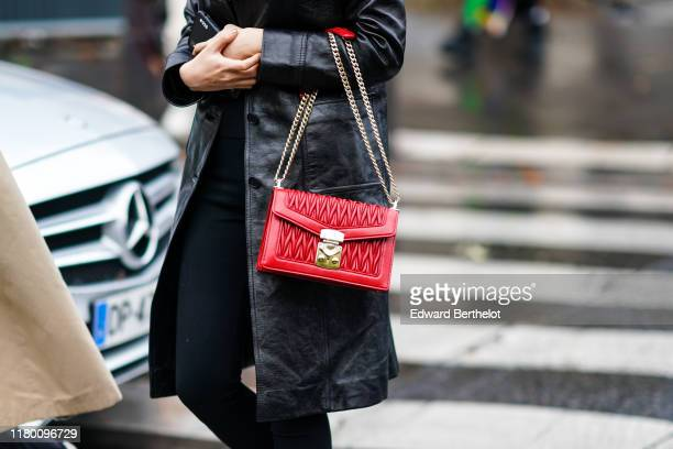 Guest wears a black leather coat, a Miu Miu red bag, outside Miu Miu, during Paris Fashion Week - Womenswear Spring Summer 2020, on October 01, 2019...