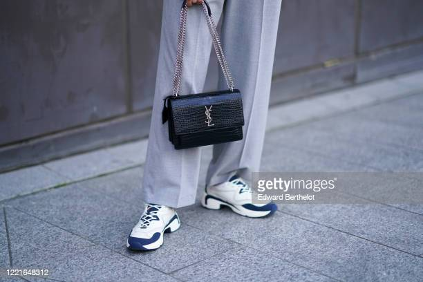 Guest wears a black leather crocodile YSL Saint Laurent bag, white and blue sneakers, during London Fashion Week February 2020 on February 17, 2020...