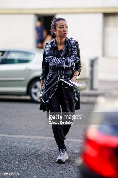 A guest wears a black leather dress with a belt and a gingham checked part outside 1017 ALYX 9SM during Paris Fashion Week Menswear SpringSummer 2019...