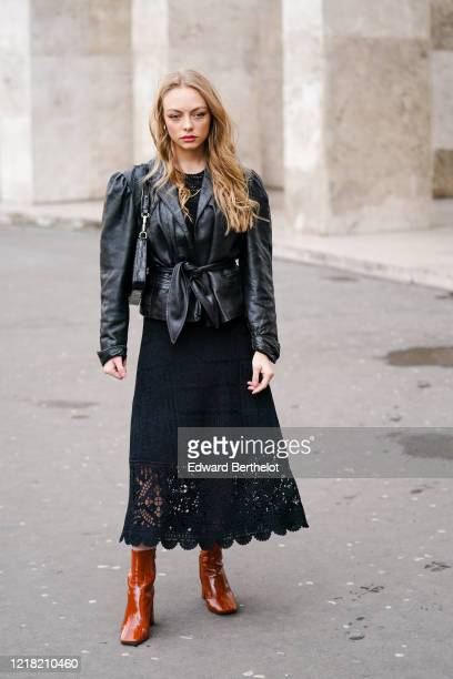Guest wears a black leather jacket, a bag, a black top, a black lace dress with embroidery, brown leather boots, outside Leonard Paris, during Paris...
