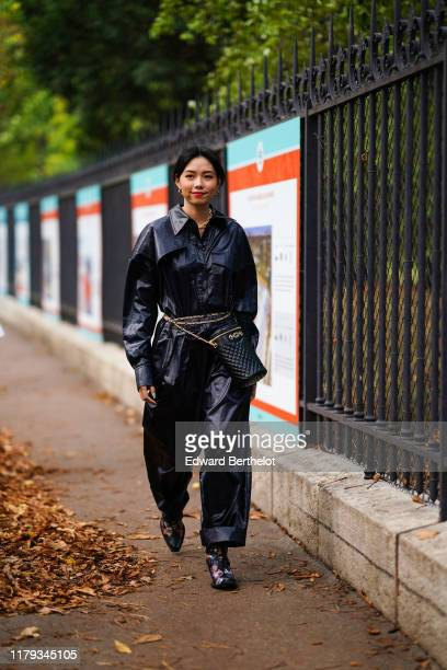 Guest wears a black leather jacket, a belt quilted bag from Gucci, black leather pants, multicolor shoes, outside Lacoste, during Paris Fashion Week...