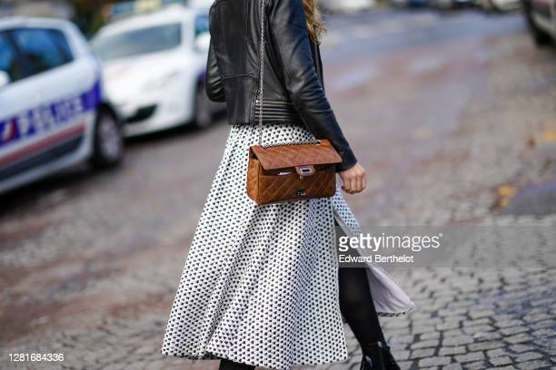 Guest wears a black leather jacket, a black and white skirt, a brown leather quilted Chanel open bag, outside Chanel, during Paris Fashion Week -...