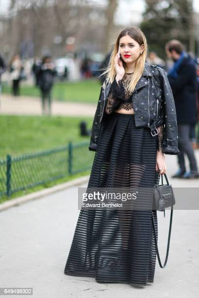 A guest wears a black leather perfecto jacket a black lace top and a black mesh skirt outside the Chanel show during Paris Fashion Week Womenswear...