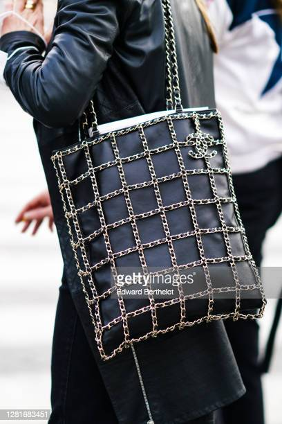 Guest wears a black leather jacket, a black leather Chanel bag with checked pattern golden chains, outside Chanel, during Paris Fashion Week -...