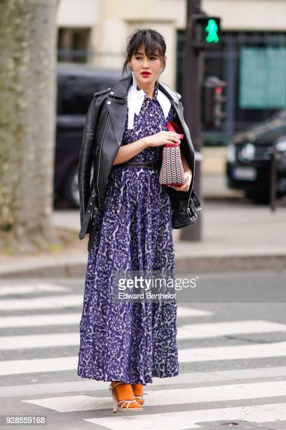 A guest wears a black leather jacket a blue dress outside Miu Miu during Paris Fashion Week Womenswear Fall/Winter 2018/2019 on March 6 2018 in Paris...