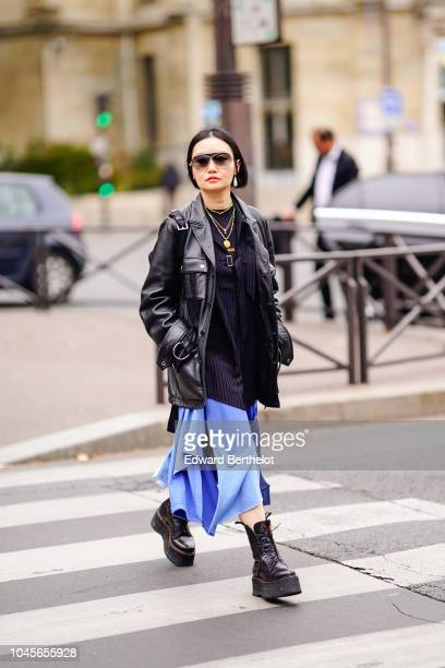 A guest wears a black leather jacket a blue dress sunglasses black boots a golden necklace earrings outside Miu Miu during Paris Fashion Week...
