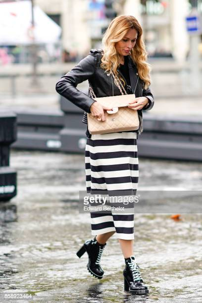 A guest wears a black leather jacket a chanel bag a striped skirt black shoes and attends Le Defile L'Oreal Paris as part of Paris Fashion Week...