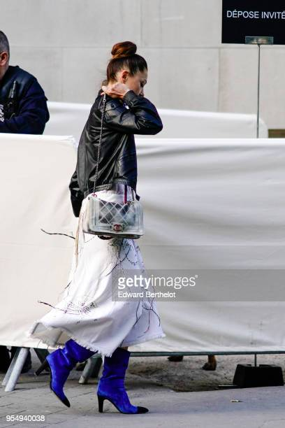 A guest wears a black leather jacket a Chanel bag a white dress with prints blue boots at Le Grand Palais on May 03 2018 in Paris France