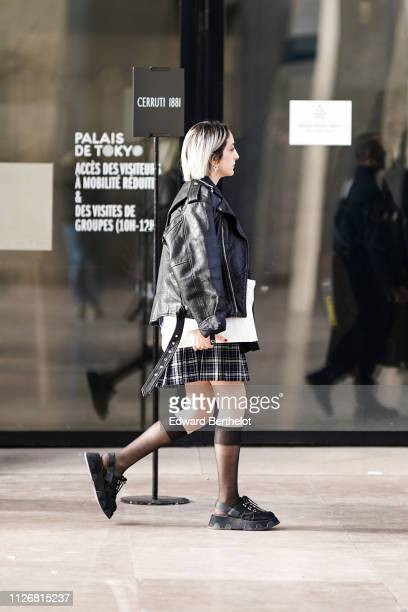 Guest wears a black leather jacket, a checked skirt, high socks, black shoes, during Paris Fashion Week - Menswear F/W 2019-2020, on January 18, 2019...