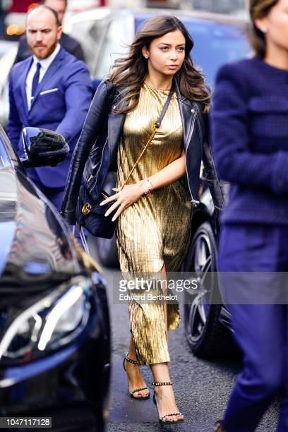 A guest wears a black leather jacket a golden shiny glitter dress heels shoes outside Valentin Yudashkin during Paris Fashion Week Womenswear...