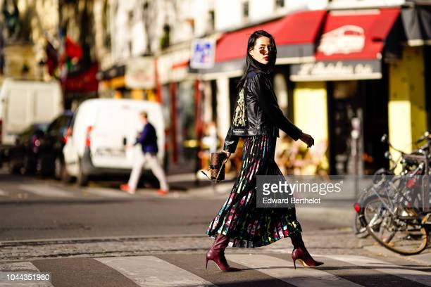 A guest wears a black leather jacket a multicolor pleated skirt outside APC during Paris Fashion Week Womenswear Spring/Summer 2019 on October 1 2018...