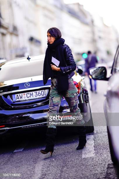 A guest wears a black leather jacket a scarf green and brown military camouflage print pants black heeled boots outside Valentin Yudashkin during...