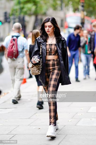 A guest wears a black leather jacket a tartan checked cropped top pants white sneakers a leopard print bag during London Fashion Week September 2018...