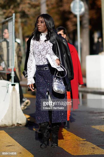 A guest wears a black leather jacket a white lace top flare pants black boots silver bag outside Chanel during Paris Fashion Week Womenswear...