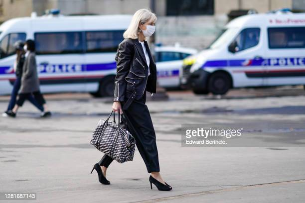 Guest wears a black leather jacket, a white t-shirt, a black and white large leather bag with printed geometric patterns, black high heeled pointy...
