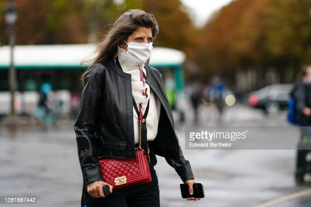 Guest wears a black leather jacket, a white vest a red leather Chanel quilted bag, black pants, outside Chanel, during Paris Fashion Week -...