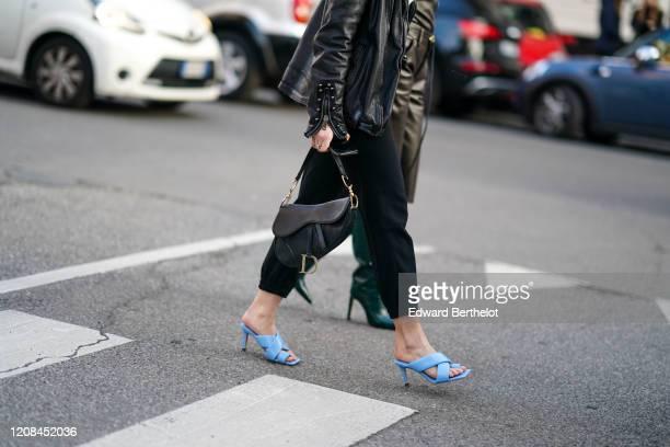 Guest wears a black leather jacket, black crop pants, a black Dior saddle bag, blue heeled sandals, outside Bottega Veneta, during Milan Fashion Week...