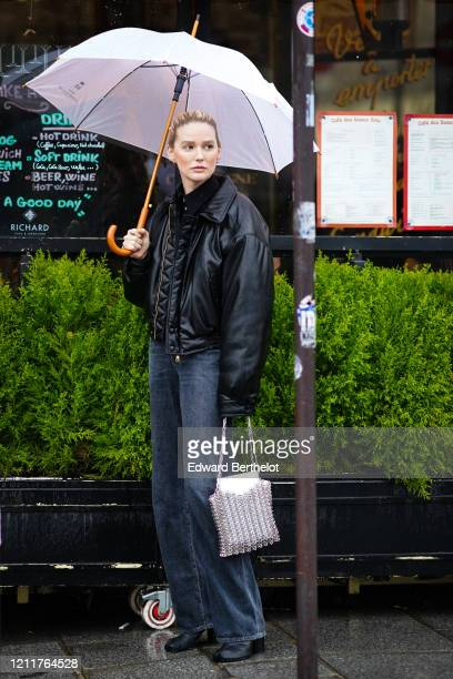 Guest wears a black leather jacket, dark gray denim jeans, a metallic bag, black leather shoes, during Paris Fashion Week - Womenswear Fall/Winter...