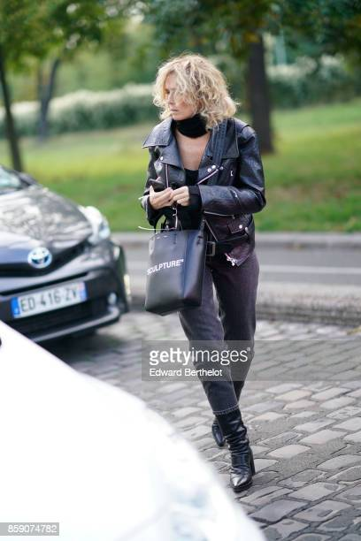 A guest wears a black leather perfecto jacket outside CDG Comme des Garcons during Paris Fashion Week Womenswear Spring/Summer 2018 on September 30...