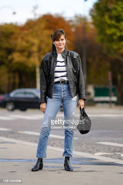 Guest wears a black leather jacket with fringes, a black and white striped pullover, a belt, blue ripped denim jeans pants, a black leather bag,...