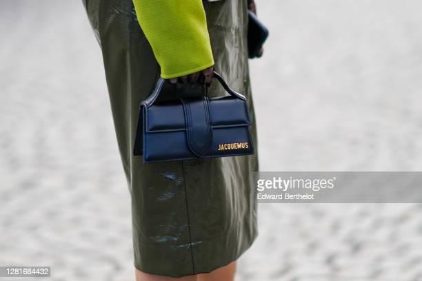 Guest wears a black leather Jacquemus bag, a green khaki shiny pvc skirt, outside Chanel, during Paris Fashion Week - Womenswear Spring Summer 2021,...