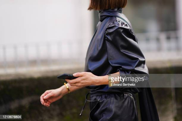 Guest wears a black leather outfit with a long scarf, outside Elie Saab, during Paris Fashion Week - Womenswear Fall/Winter 2020/2021, on February...