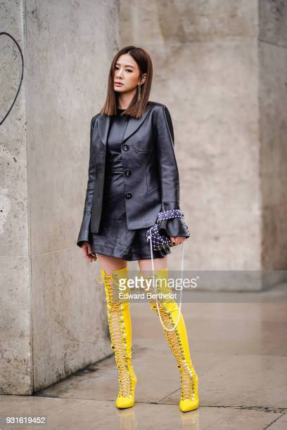 A guest wears a black leather pagoda sleeves jacket a black leather dress a beaded black shoulder bag yellow laceup overknee boots during Paris...