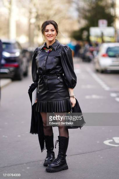 Guest wears a black leather pleated dress, colored necklace, a bag, tights, boots, outside Elie Saab, during Paris Fashion Week - Womenswear...