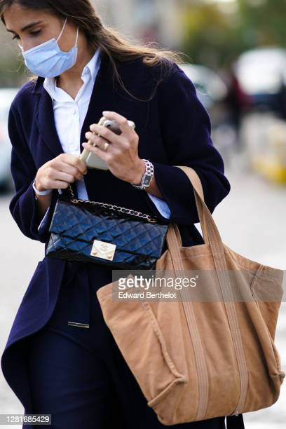 Guest wears a black leather quilted Chanel bag, a brown large tote bag, outside Chanel, during Paris Fashion Week - Womenswear Spring Summer 2021, on...